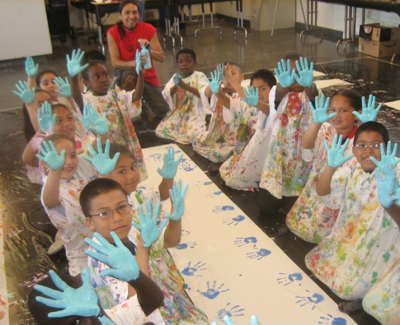 Freese Elementary first graders starting to paint a giant puppet with teaching artist Felix Diaz. University of California eScholarship Repository, CC BY