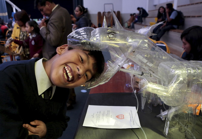 A student jokes with a dinosaur robot built with recycled materials during the annual robotics fair supported by the Bolivian Education Ministry in La Paz, August 10, 2015. REUTERS/David Mercado - RTX1NT9X